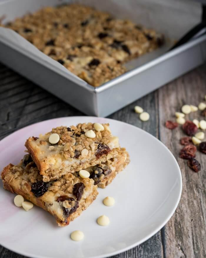 white chocolate cranberry oat bars stacked on a white plate