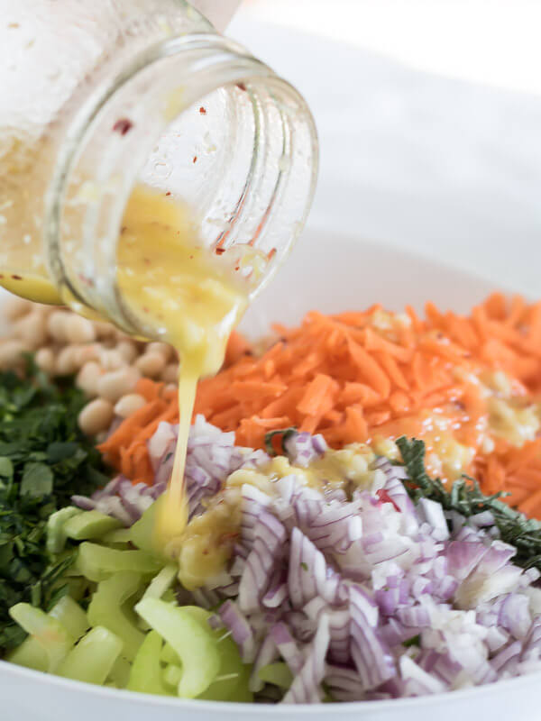 pouring lemon herb dressing over easy bean salad ingredients