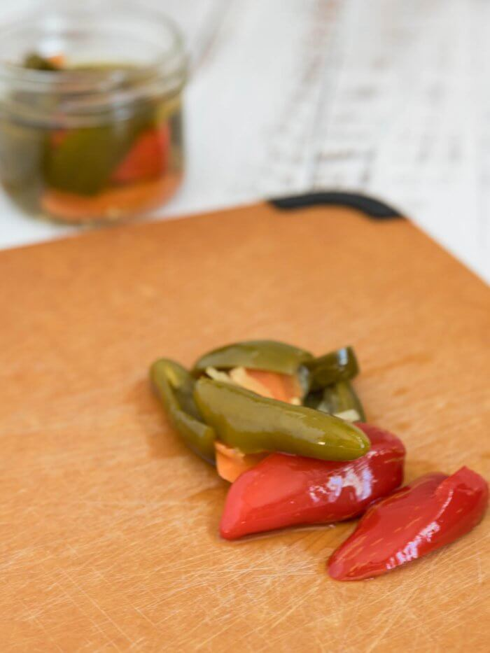 pickled whole jalapeno's on a cutting board