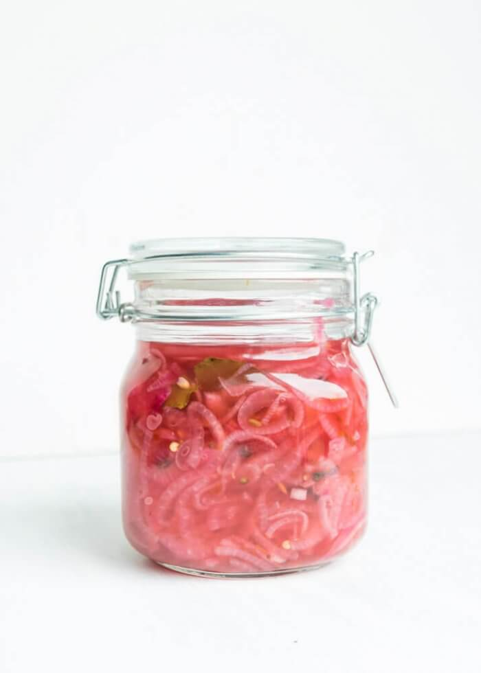 Picked red onions in a glass jar