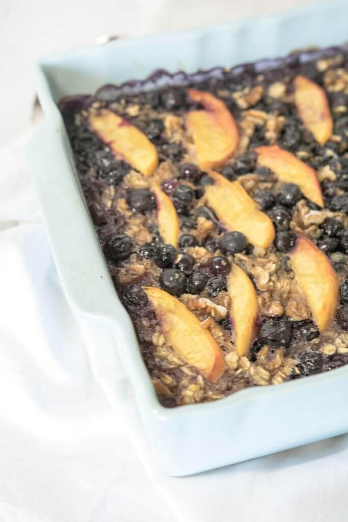 baked banana oatmeal with blueberries and sliced peaches
