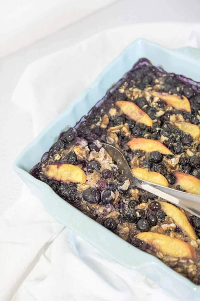baked oatmeal in a blue casserole with blueberry and peaches