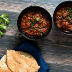 two bowls of black bean and chipotle stew served ith pita bread
