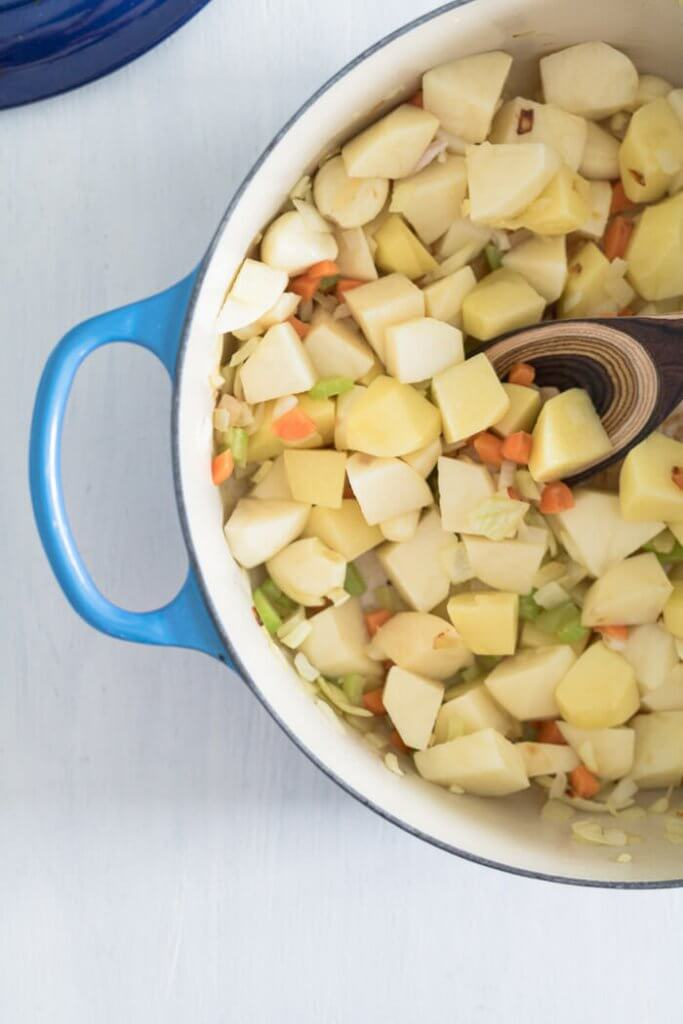 garlic cloves and potatoes and vegetables in a soup pot