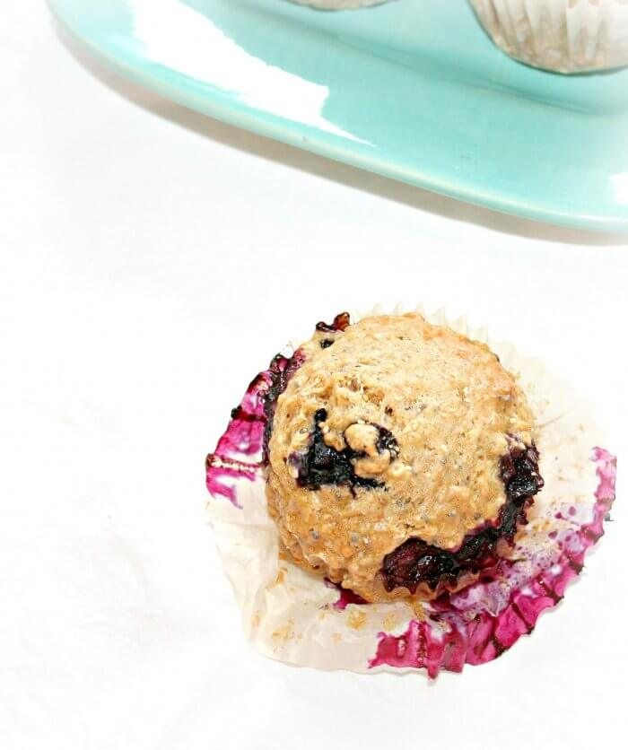 vegan blueberry muffin on a white background with a blue plate