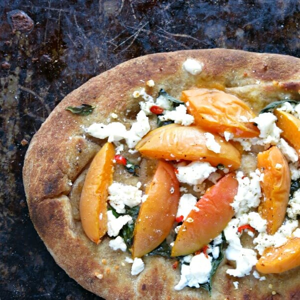 flatbread with apricots and goat cheese on a baking tray