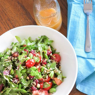 arugula, edamame, beet and date salad with jar of grapefruit viniagrette