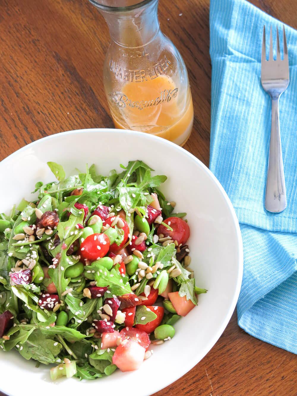 arugula, edamame, beet and date salad with jar of grapefruit viniagrette