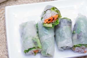 vegan fresh salad wraps stacked on a square white plate