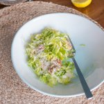 shaved brussel sprouts with parmesan and walnuts in a white bowl, fork
