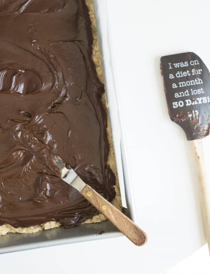 spreading fudge on top of oat cookie crust