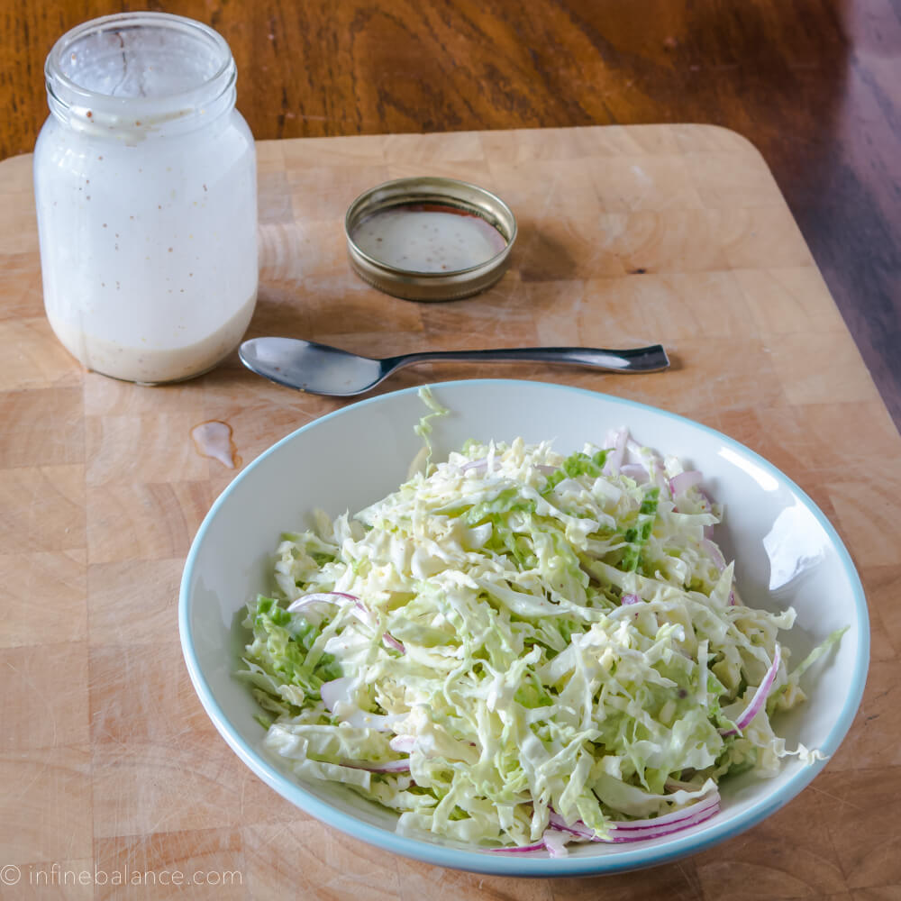 savoy cabbage slaw in a white bowl with a jar of creamy viniagrette