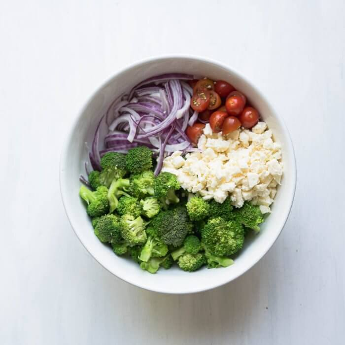 salad bowl with feta cheese,cherry tomatoes, red sliced onions and blanched broccoli