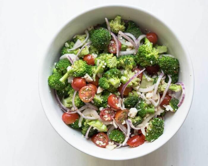 large bowl of broccoli salad with cherry tomatoes and feta cheese