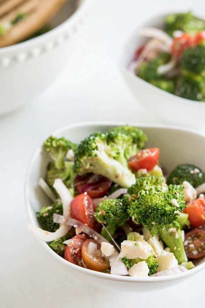 two bowls of broccoli and feta cheese salad with cherry tomates