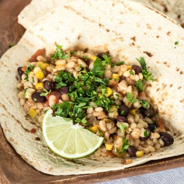 whole grain torilla filled with black bean and barley burrito filling with lime on a wood plate