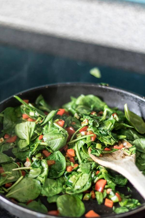 spinach and red peppers in saute pan to make a frittata, it's all made in one pan