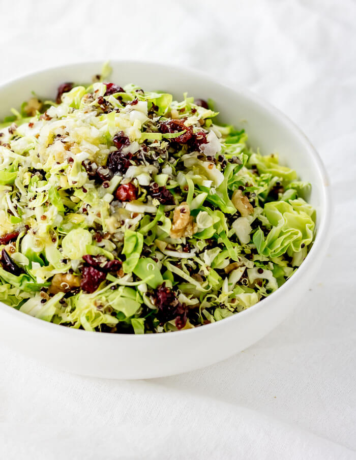 raw brussels sprout and quinoa salad with cranberries and walnuts in a white bowl