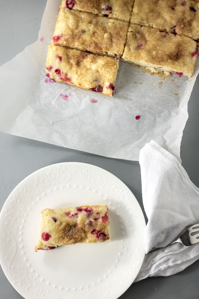 cranberry snack cake, top view, with full cake on parchment and one slice of cake on white plate