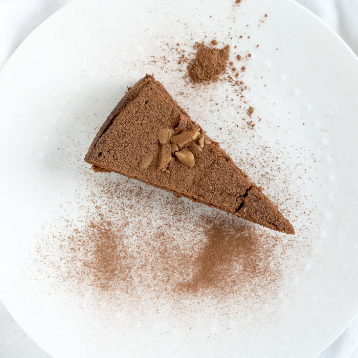 a slice of dark chocolate ricotta cake on a plate with cocoa