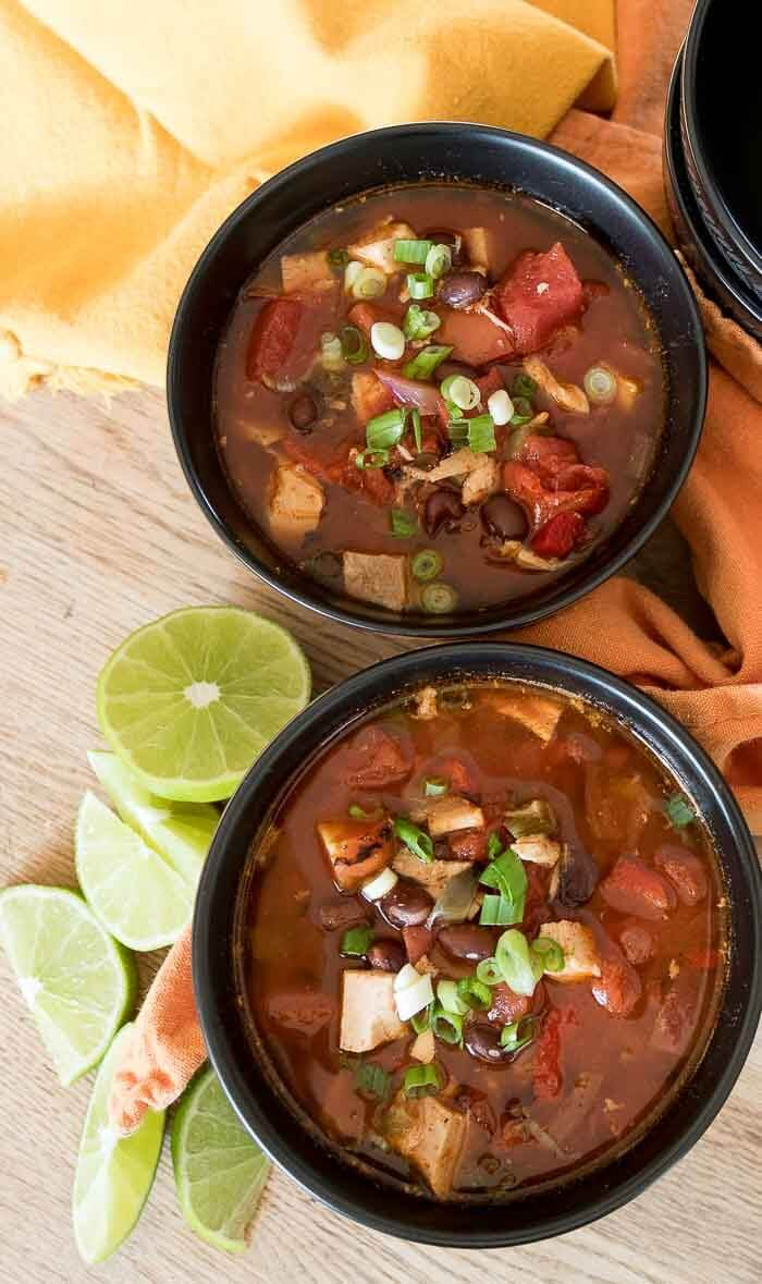 two bowls of turkey enchilada soup with blackbeans and  limes