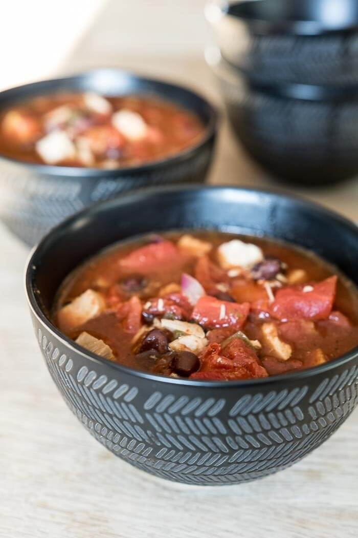 two bowls of tomato based turkey soup with black beans in black bowls