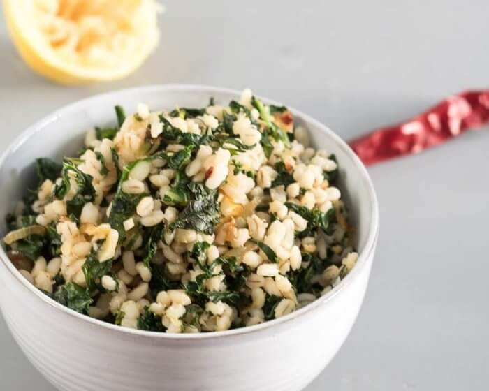 barley with lemon and kale in a white bowl, lemon and chili pepper in background