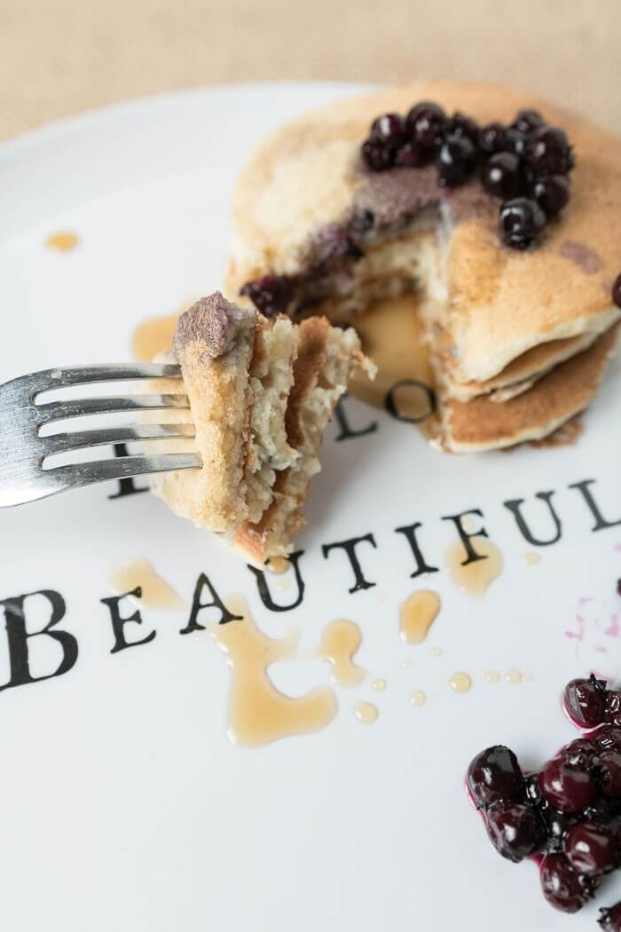 a stack of banana pancake with blueberries with a bite