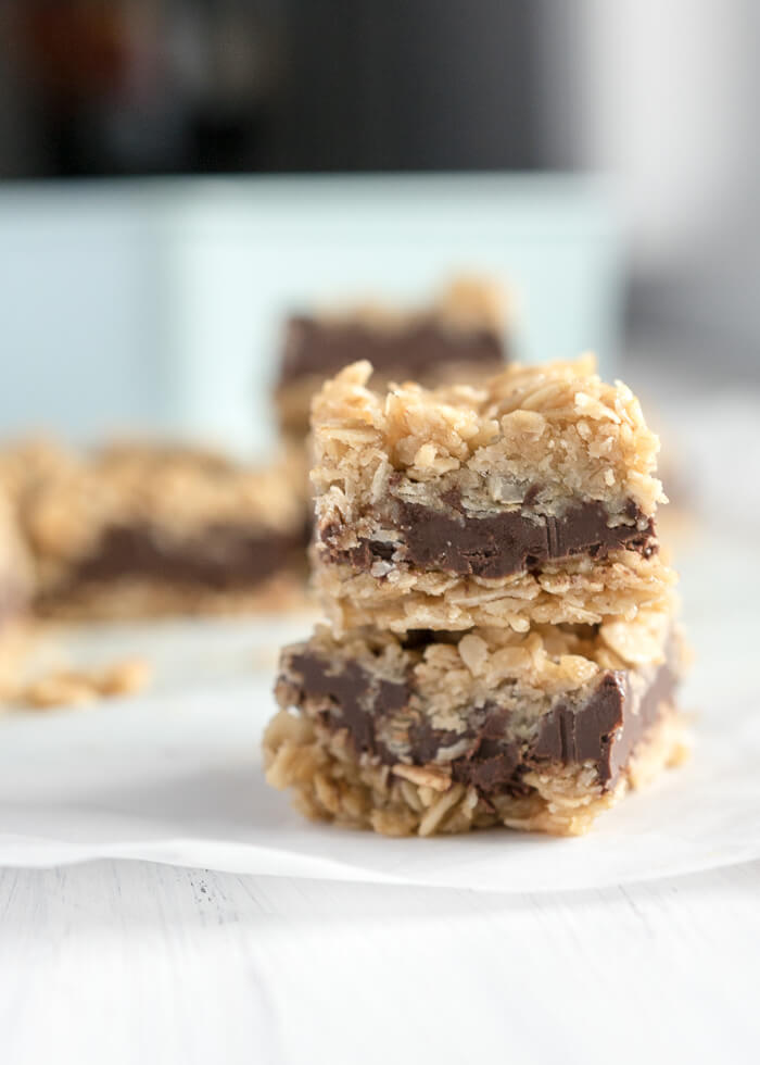no bake chocolate oat bars in a stack on parchment paper