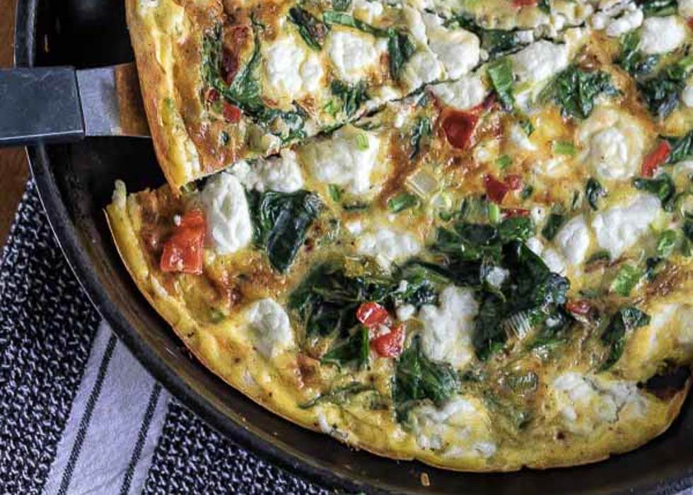 spinanch and goat cheese frittata in a skillet