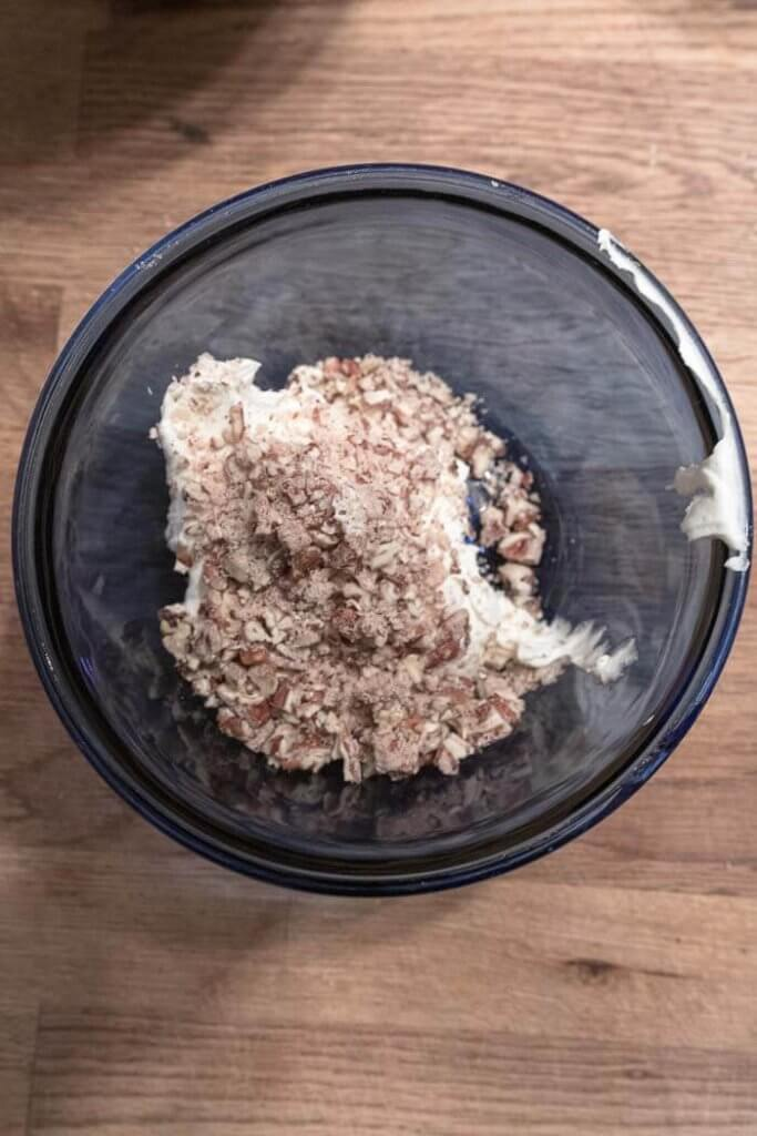 folding pecans into whipped frosting to make cake filling