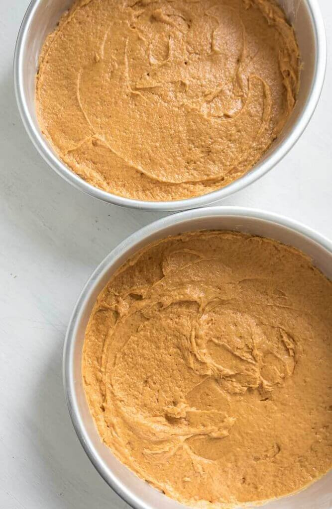 pumpkin cake batter in cake pans