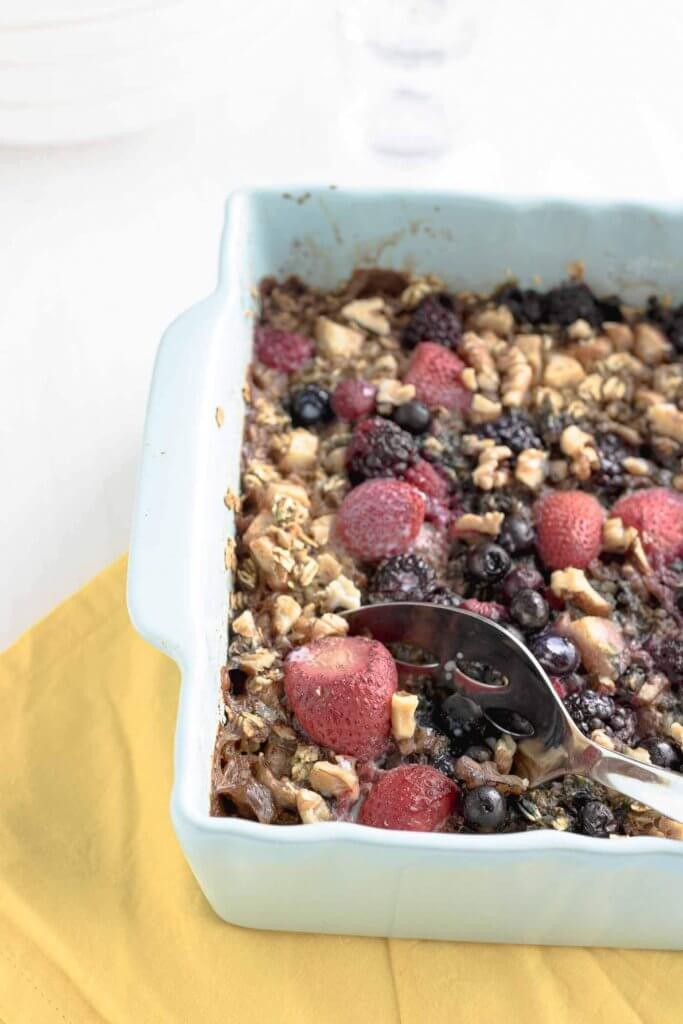 berry baked oats in a baking dish with a serving spoon and yello napkin