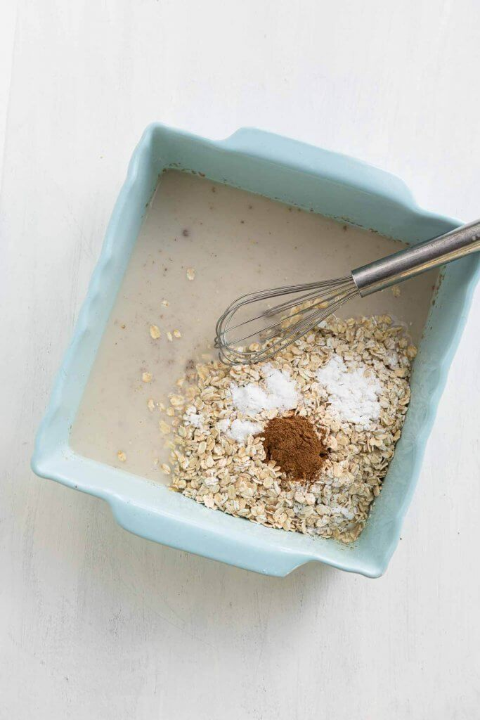 baking dish with almond milk and flax with oats, cinnamon and baking soda before mixing