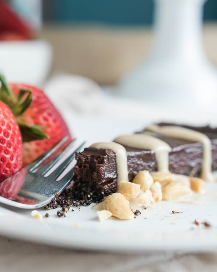 a slice of vegan chocolate pie on a white plate with berries and peanut butter sauce