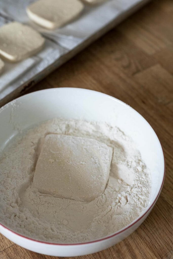 dregding tofu in flour for fried tofu sandwiches