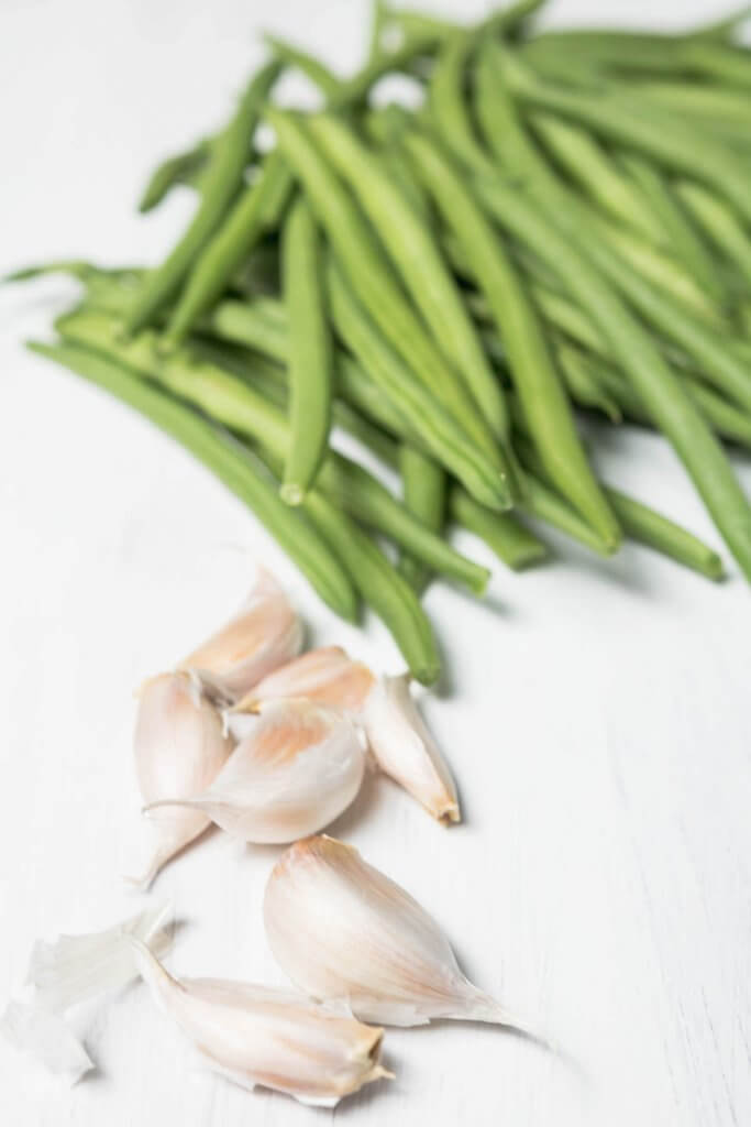 fresh garlic and green beans on a white board