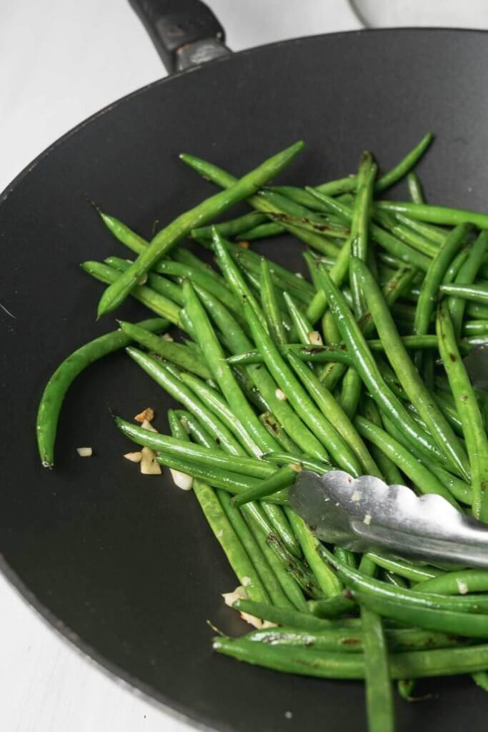 in a large wok, green beans with garlic