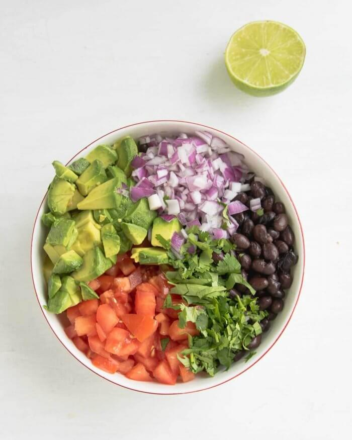 oil free black bean salsa ingredients in a bowl with a lime