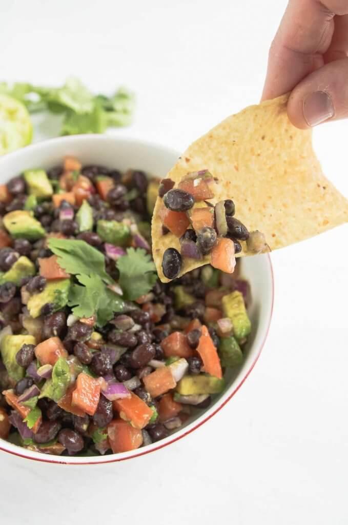 a tortilla chip dipping into a bowl of black bean avocado dip