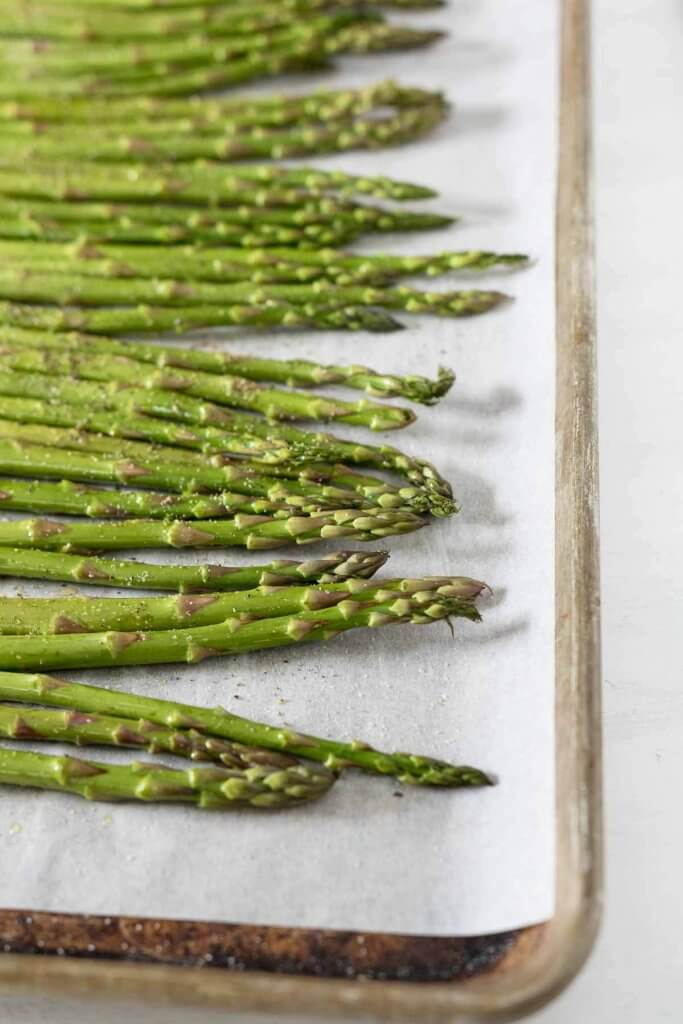 asparagus ready for oven roasting on a parchement lined baking sheet