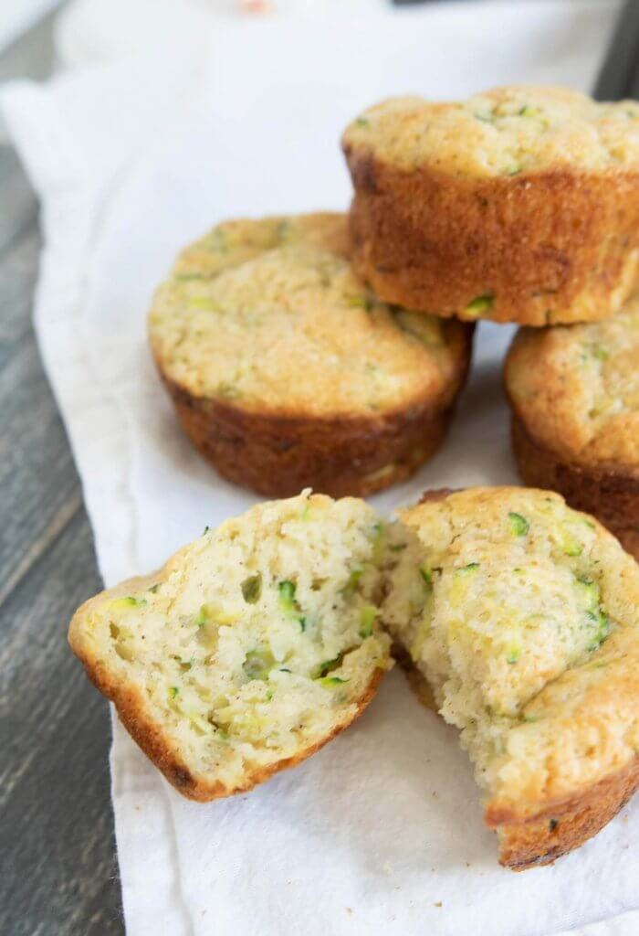 a stack of zucchini muffs with one muffin broken so you can see the green flecks of zucchini inside