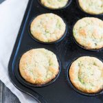 zucchini muffins in a black muffin baking tin