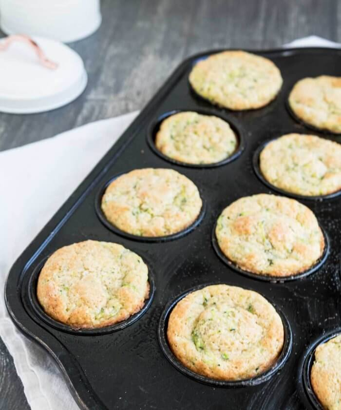 a muffins baking tray full of zucchini muffins with lemon