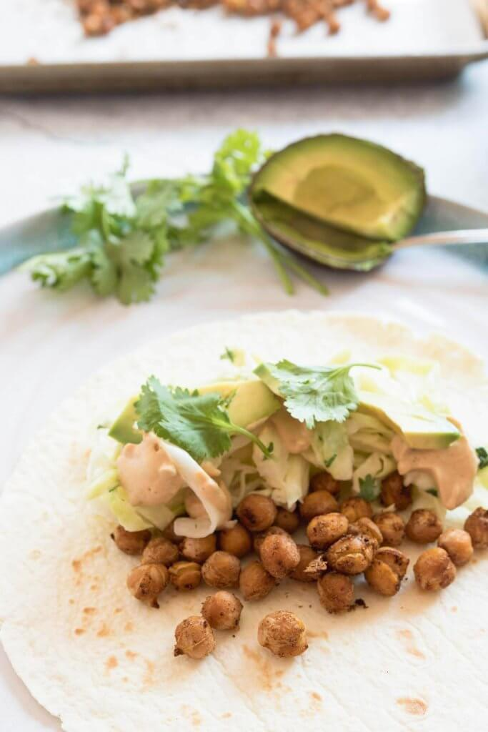 soft taco shell with roasted taco spiced chickpeas, slaw and avocado
