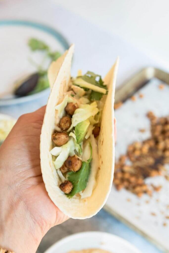 a hand holding a chickpea taco topped with jalapeno cole slaw and avocado