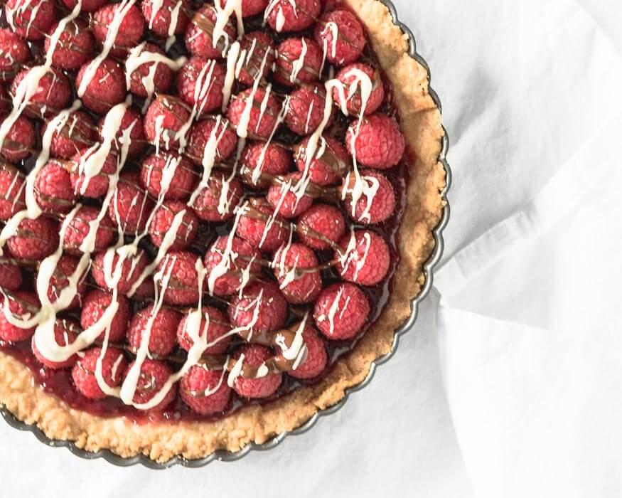 fresh raspberry tart drizzled with white and dark chocolate