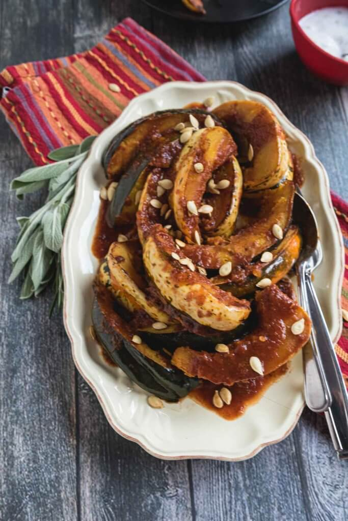 slow cooker acorn squash on a serving platter and served with sweet and spicy tomato sauce