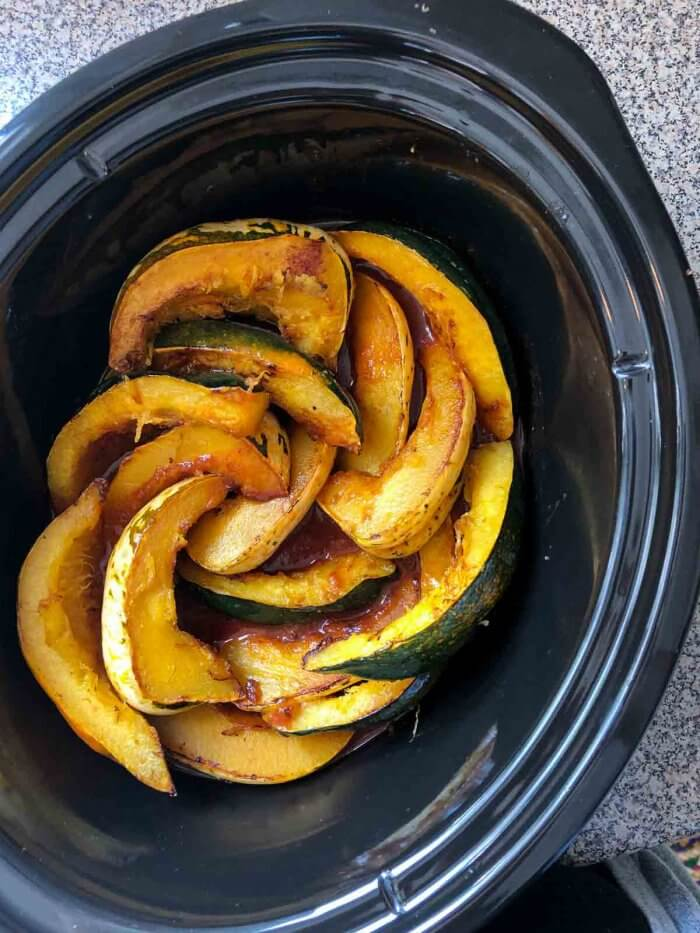 browned acorn squash layered in a slow cooker with spicy tomato sauce