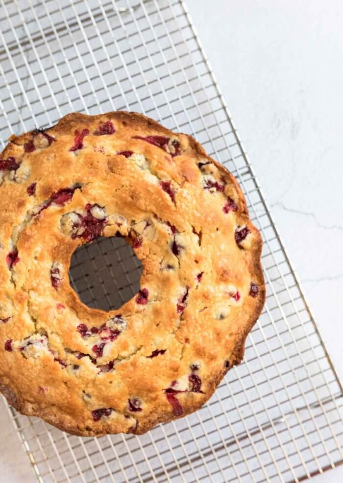 cranberry bundt cake removed from cake pan and on a cooling rack to cool completely before adding glaze